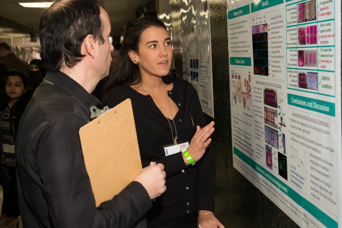 Student presenting poster to faculty judge