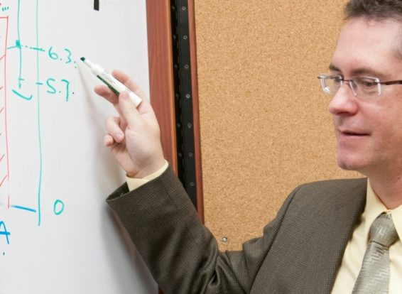 Faculty writing on white board